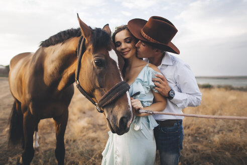 Caucasian cowboy kissing woman on cheek near horse - BLEF02884