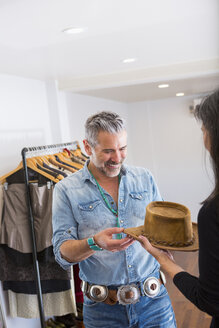 Woman showing hat to man in store - BLEF02911