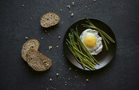 Bread and crumbs near plate with fried egg and asparagus - BLEF02968
