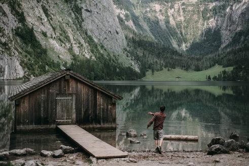 Caucasian man skipping stones in mountain lake - BLEF02989