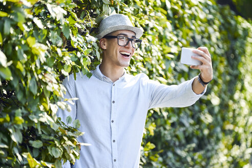 Happy young man taking selfie in a hedge - BSZF01064