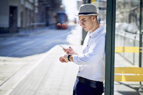 Young man checking time at a tram stop in the city - BSZF01067