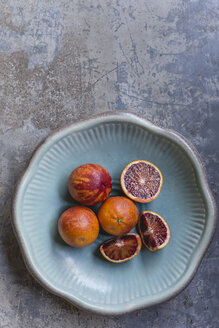 Whole and sliced blood oranges in a bowl - STBF00331