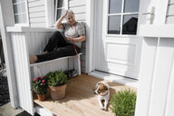 Relaxed senior woman sitting on porch with her dog - KMKF00914