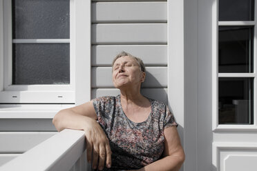 Relaxed senior woman sitting on porch in sunshine - KMKF00917