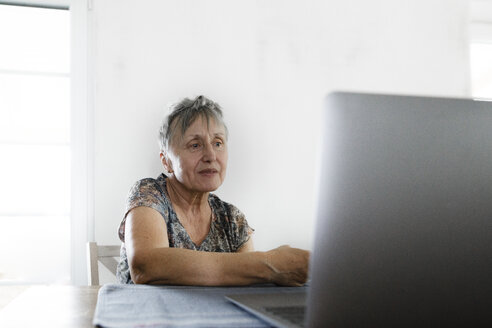Senior woman sitting at table at home using laptop - KMKF00920