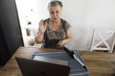 Senior woman sitting at table at home with laptop and curling iron - KMKF00923