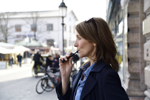Mature woman smoking electronic cigarette in the city - ECPF00684