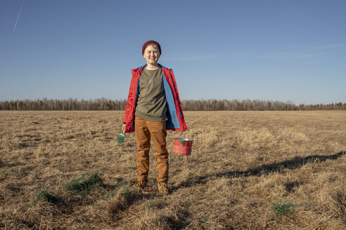 Portrait of smiling boy with paint bucket and brush in steppe landscape - VPIF01217