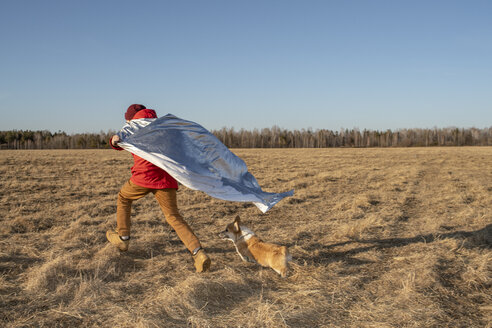 Boy dressed up as superhero running with dog in steppe landscape - VPIF01226