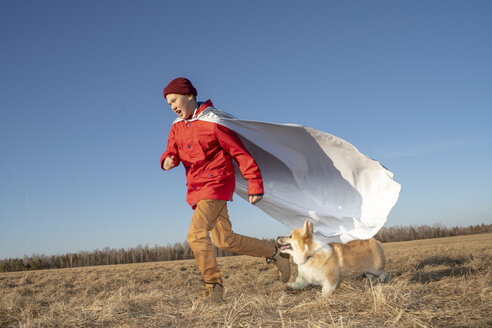 Boy dressed up as superhero running with dog in steppe landscape - VPIF01232