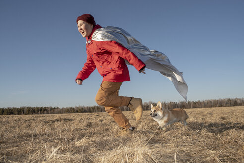 Boy dressed up as superhero running with dog in steppe landscape - VPIF01235