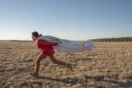 Happy boy dressed up as superhero running in steppe landscape - VPIF01247