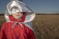 Hood of superhero costume covering boy's face in steppe landscape - VPIF01253