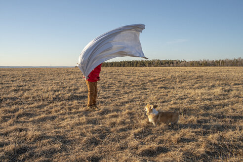 Dog and boy with superhero costume in steppe landscape - VPIF01256