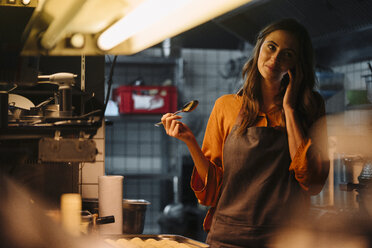 Young woman talking on cell phone in restaurant kitchen - KNSF05760