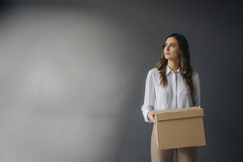 Serious young businesswoman holding cardboard box - KNSF05781
