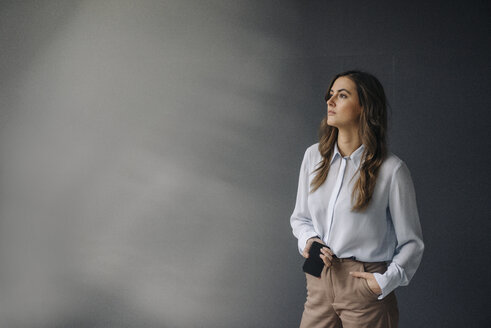 Portrait of serious young businesswoman with cell phone looking sideways - KNSF05784
