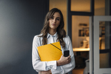 Portrait of serious young businesswoman holding folder and cell phone - KNSF05799