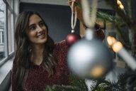 Smiling young woman decorating Christmas tree - KNSF05805