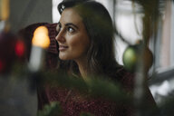 Young woman at decorated Christmas tree looking away - KNSF05811
