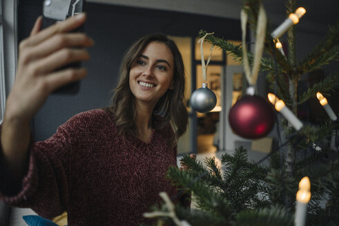 Smiling young woman taking a selfie at Christmas tree - KNSF05814