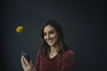 Smiling young woman using flower as antenna for cell phone - KNSF05817