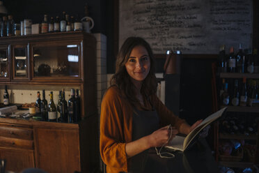 Portrait of smiling young woman with book at restaurant counter - KNSF05820