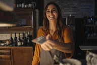 Smiling young woman at restaurant counter handing over credit card - KNSF05823