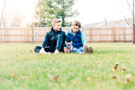 Children playing with puppy on grass - ISF21248