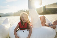 Girls playing on inflatable swan in lake - ISF21275