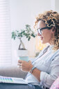 Smiling woman with coffee mug using laptop on couch at home - SIPF01952