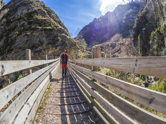 Spain, Asturia, Cantabrian Mountains, senior man on a hiking trip crossing a bridge - LAF02310