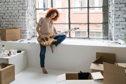 Mid adult woman moving into industrial style apartment, sitting on window ledge playing guitar - CUF50513