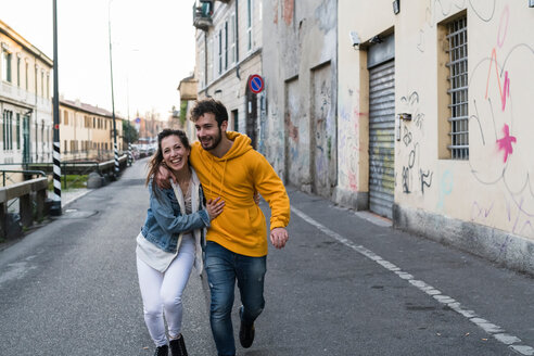 Happy young couple walking down alleyway with arms around each other - CUF50543