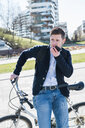 Man talking on smartphone, leaning against bicycle, Milan, Lombardia, Italy - CUF50585