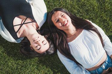 Friends lying down on grass - CUF50627
