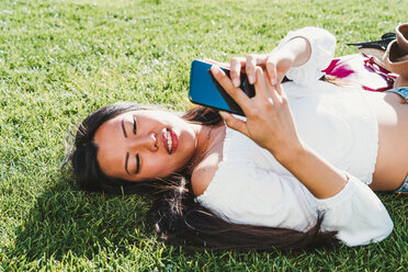 Woman lying down, using smartphone on grass - CUF50630