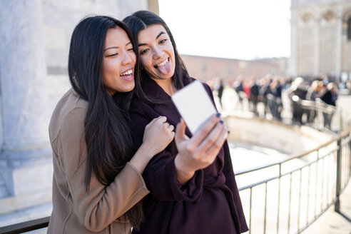 Friends taking selfie and sticking out tongue at smartphone, Pisa, Toscana, Italy - CUF50639
