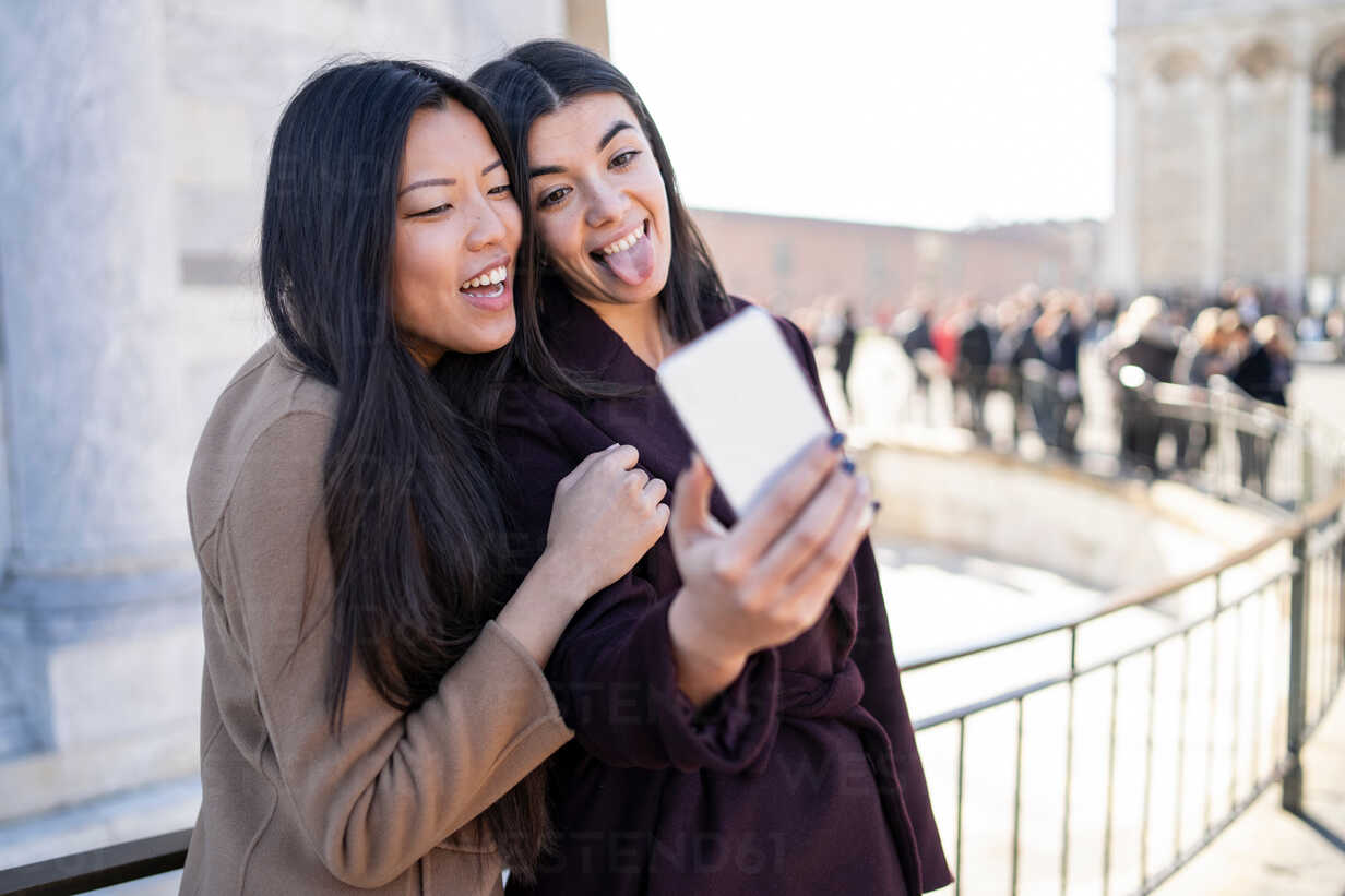 Friends taking selfie and sticking out tongue at smartphone, Pisa, Toscana, Italy - CUF50639 - Francesco Buttitta/Westend61