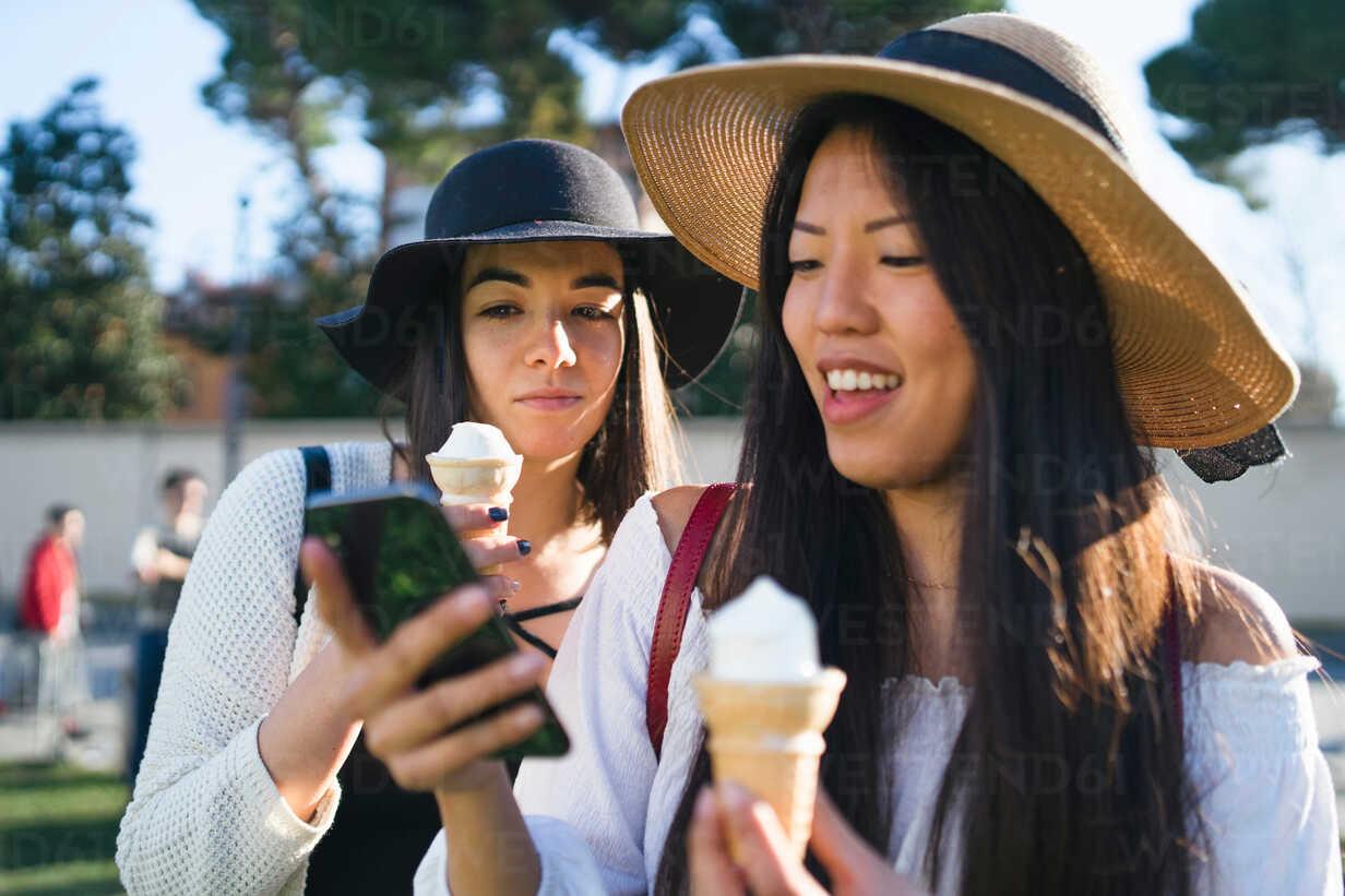 Friends with ice cream cones, using smartphone - CUF50645 - Francesco Buttitta/Westend61