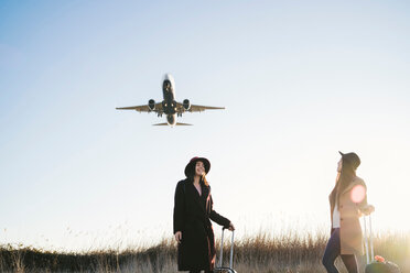 Friends waiting with wheeled luggage on roadside, airplane flying above - CUF50651
