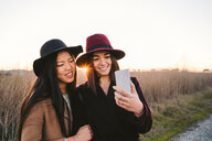 Friends taking selfie on roadside - CUF50657