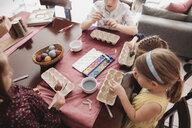 Children painting Easter eggs on table at home - KMKF00927