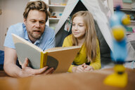 Father and daughter at home reading book in children's room - KNSF05844