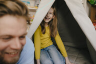 Happy father and daughter with teepee in children's room - KNSF05847