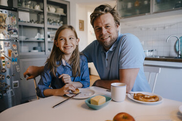 Portrait of father and daughter at home sitting at breakfast table - KNSF05850