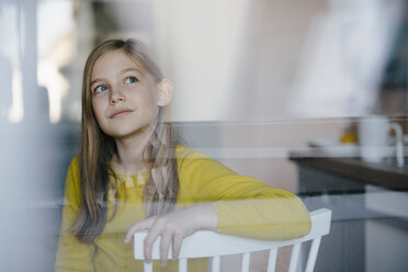 Portrait of a girl sitting on chair at home looking up - KNSF05862