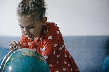 Girl at home looking at globe - KNSF05865