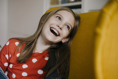 Laughing girl in armchair at home - KNSF05868